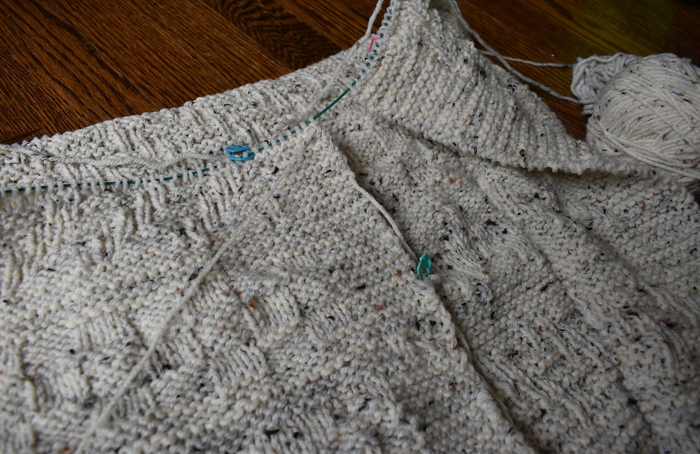 A cream gansey blanket with a progress keeper and stitch marker