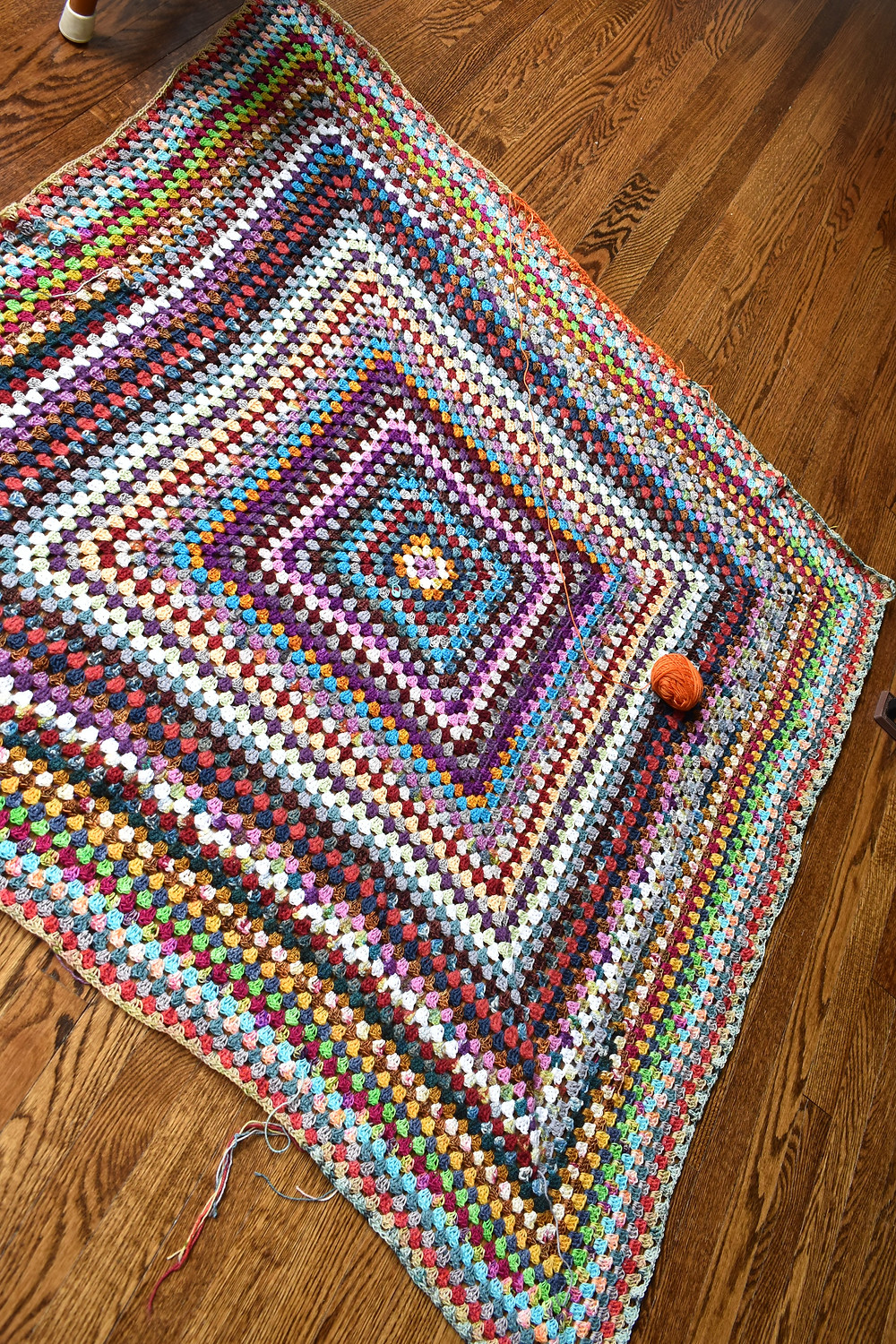 Multi colored Granny Square crocheted afghan on oak floor