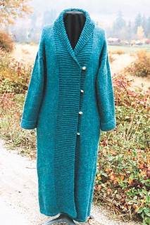 A blue full length double breasted wool coat with silver buttons and a garter-stitch shawl collar