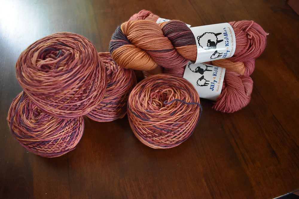 7 skeins of yarn in pinks, peaches and golds. Four are wound into cakes, 3 are in the original hank. Background is a dark wood table.