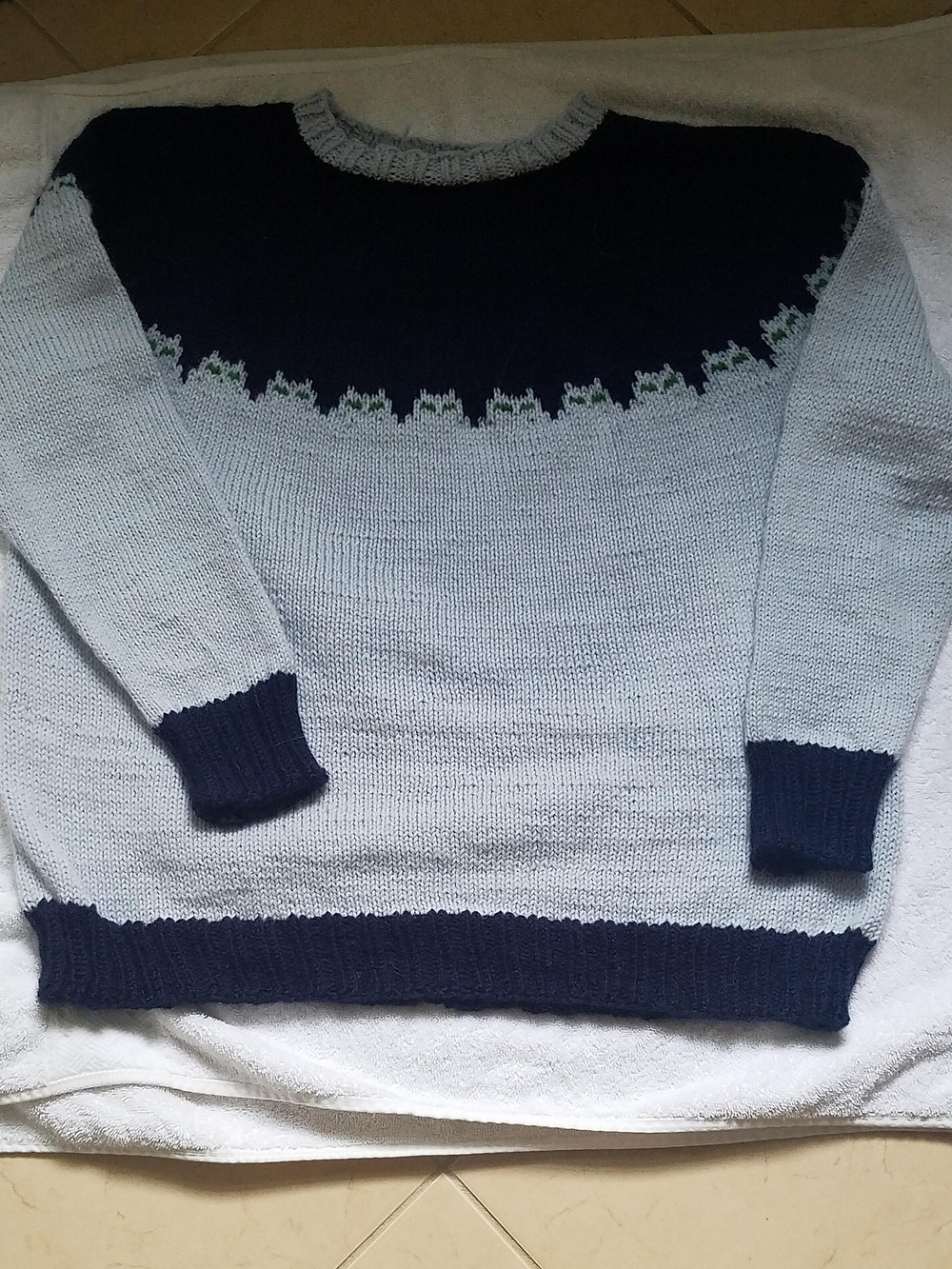 Picture of a long-sleeved light blue grey sweater with a navy-blue yoke and multiple green eyed cats where the yoke and body meet.
