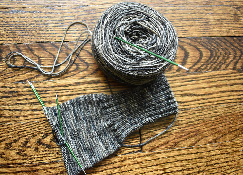 Multicolored knit sock in greys on green dpns against wood floor.