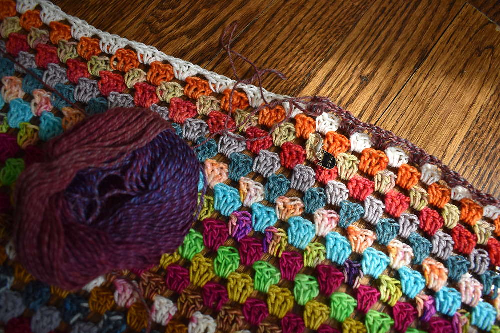Multi colored fingering weight granny square blanket and ball of yarn