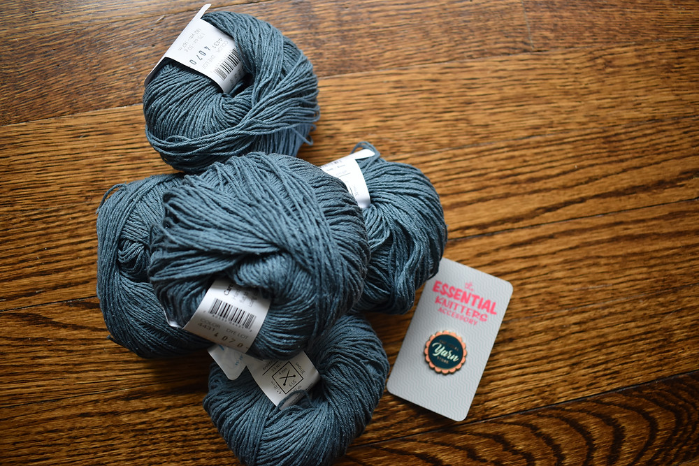 5 balls of luminous blue silk yarn and a pin from the Local Yarn Store