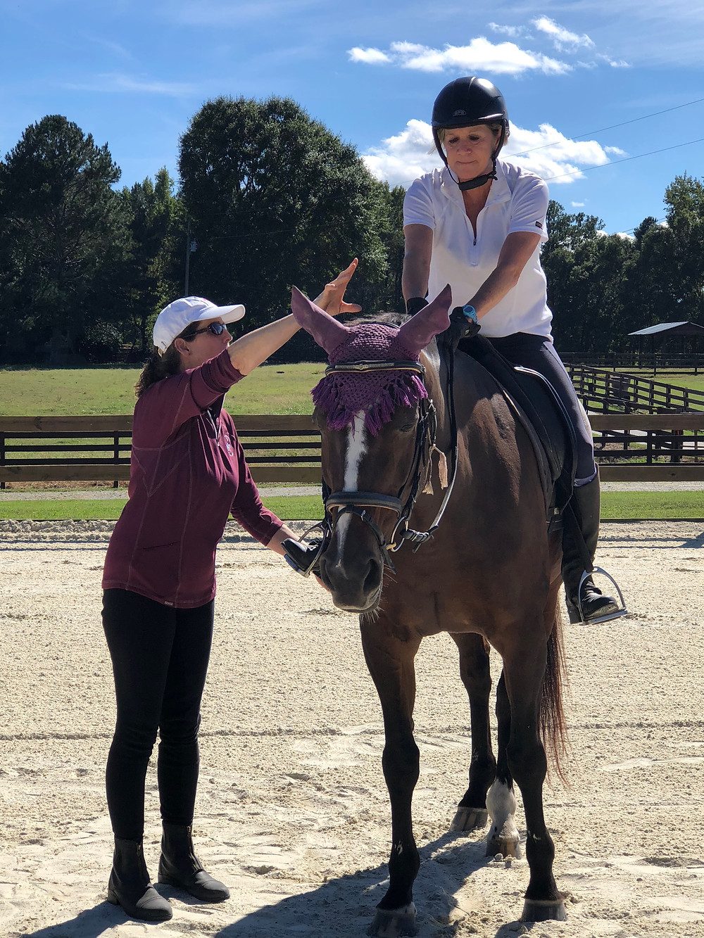 Catherine Hunter of Sacred Connections Horsemanship adjusting a rider's position.