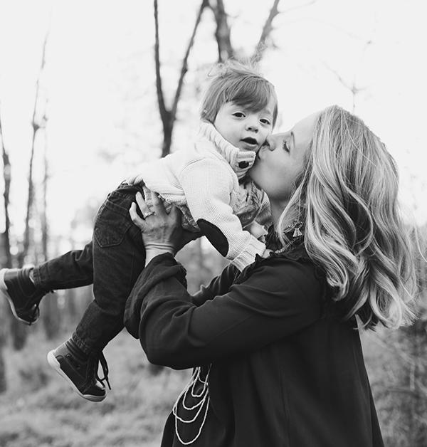 svartvit bild på moder som pussar sitt barn