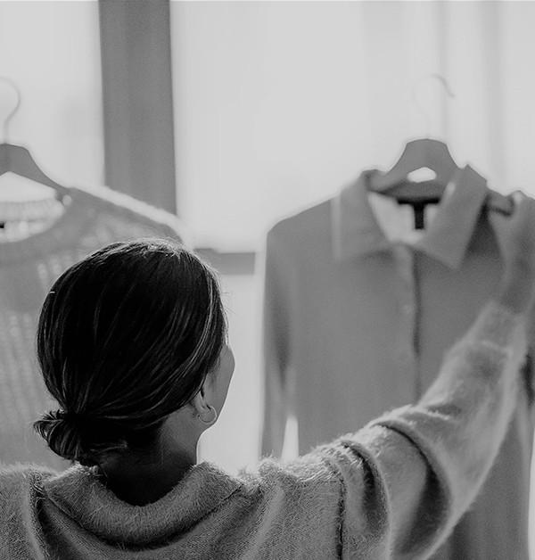 Svartvit bild på kvinna som håller upp klädesplagg