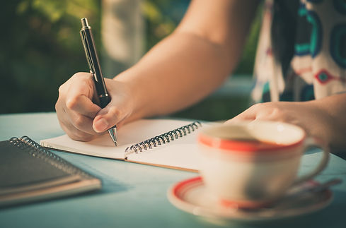 Woman hand writing journal on small note