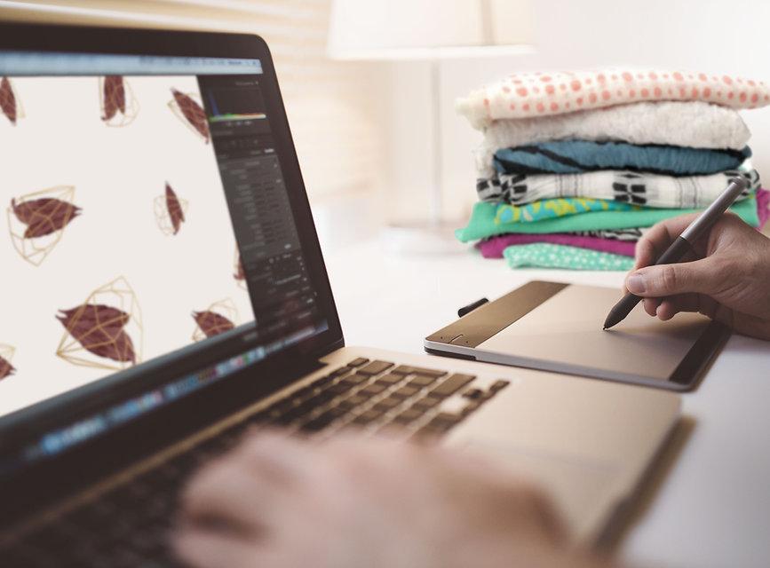 Foto mano de mujer trabajando en computador con ropa doblada al lado