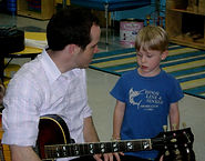 A kindergartener asks a Soyulla guitar teacher about his instrument
