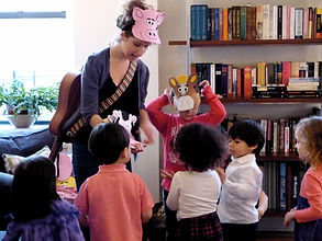 Kids dress up like farm animals to sing Old MacDonald at a party with guitar player and singer