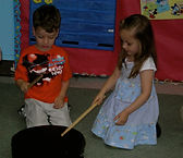A young boy and girl get to play with a drum and drumsticks to learn about music