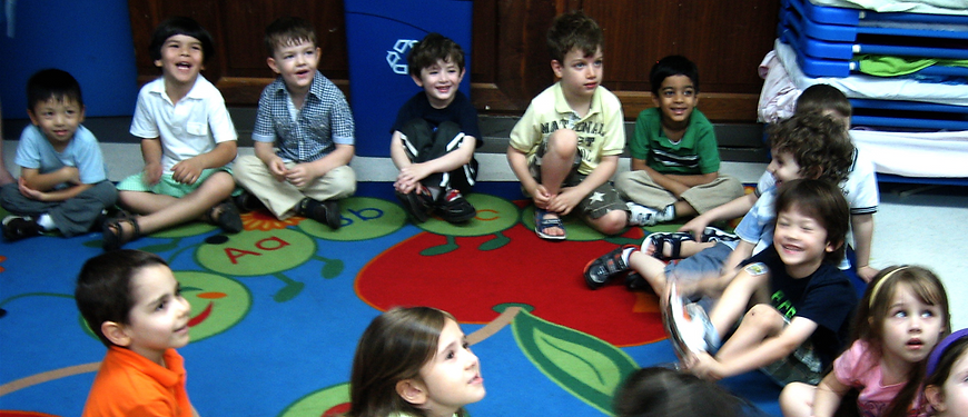 Children sit attentively and laugh as a Soyulla music teacher shows them a fun instrument