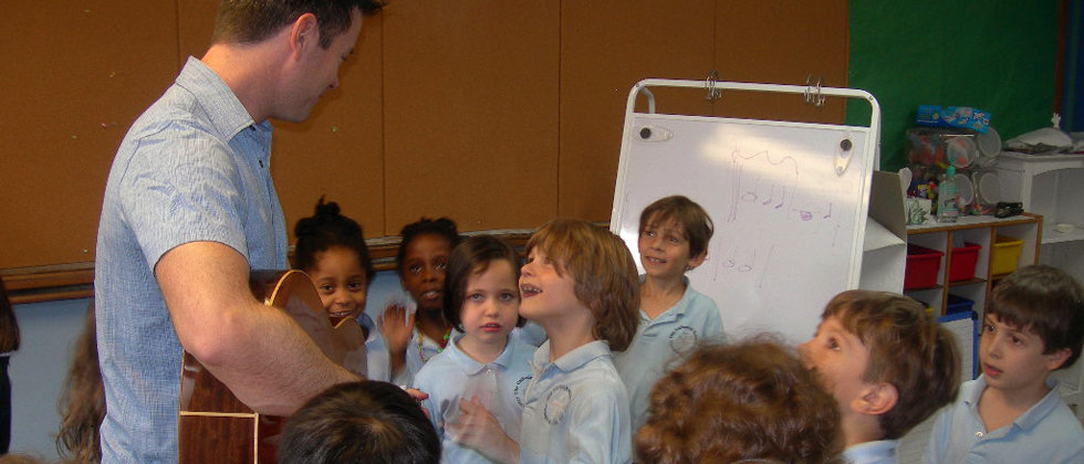 Soyulla Center Stage guitar teacher showing children at a private elementary school how to write music notes, rhythm, fun while playing music to develop their ear