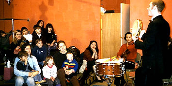 Kids and their parents listen to an interesting presentation on drums and tambourine