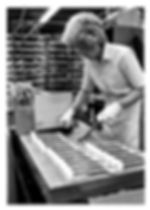 Woman working on piano foot pedals on an assembly line