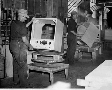 Employees assembling wooden television cabinets