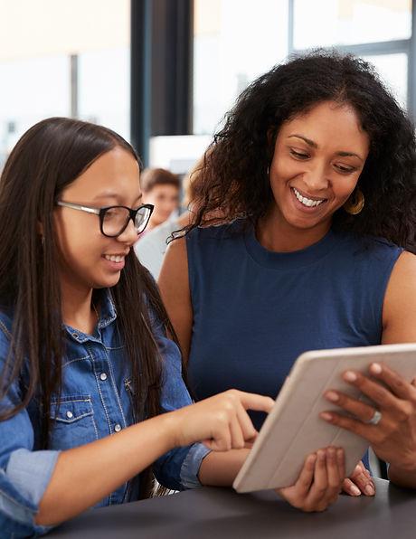 Teacher helping teenage schoolgirl with