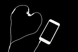 Headphones and phone on black background