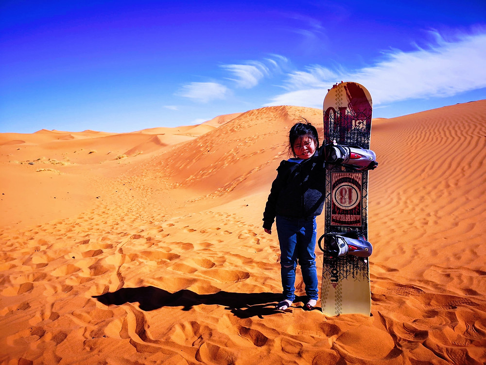 Little girl with sand board in Sahara Desert