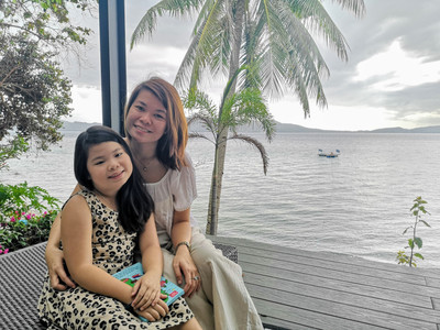Mother and Daughter enjoying a sunny afternoon with sea as background