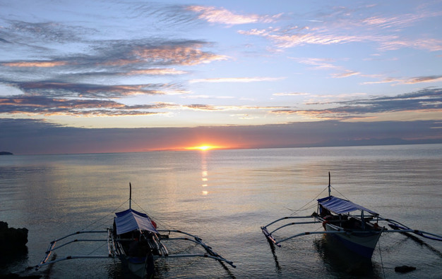 Boats at bay with sunset in background in Romblon