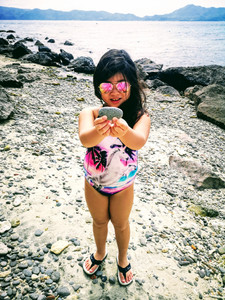 Girl with sunglasses holding a rock at the beach