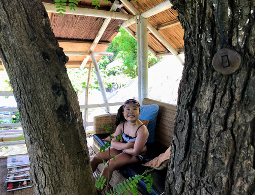 Little girl smiling and playing at the tree house