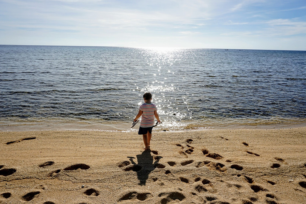 Little girl with slippers in hands walking on the beach of Romblon