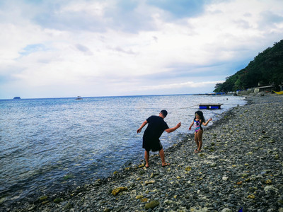 Father and daughter playing skipping stones at the beach