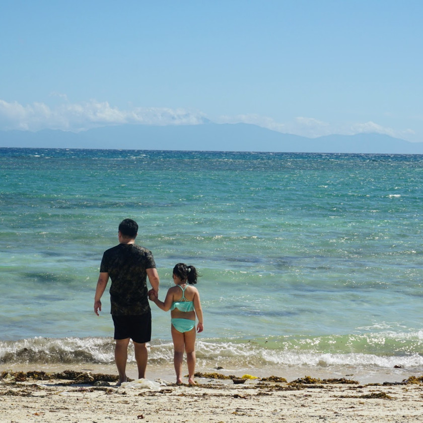 Father and daughter standing on Aglicay beach of Romblon