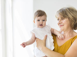 Mature woman embrace with baby girl. Gra