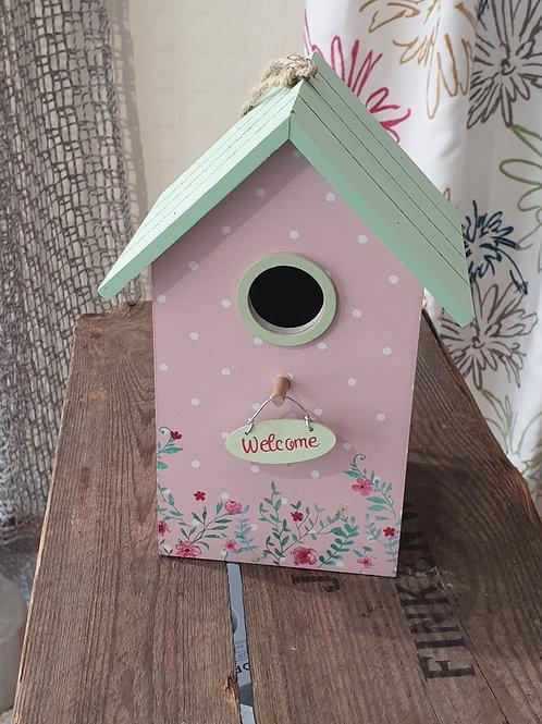 kleines Vogelhaus mit pinker Fassade und grünem Dach