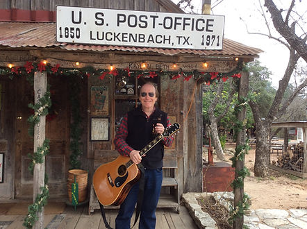 "Christmas in Luckenbach.  Singer/songwriter Randy Brooks and guitar, about to head inside and lead visitors in singing ""Grandma Got Run Over by a Reindeer."""