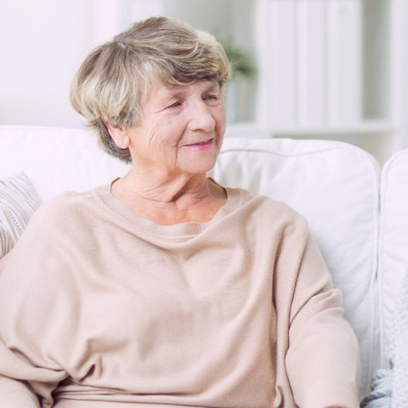 A mature woman sitting on a sofa and smiling