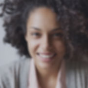 a woman in a grey cardigan smiling happily
