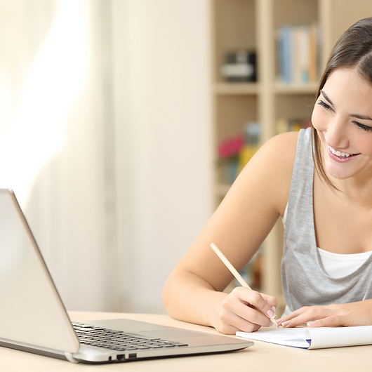 A young woman happily taking notes from an online course on her laptop