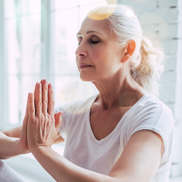 a senior woman with hands in namaste prayer position, meditating