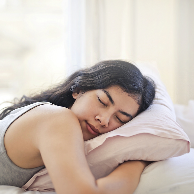 A happily sleeping woman, eyes closed, hugging her pillow