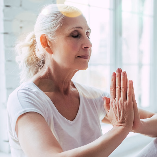 A senior woman with hands in namaste prayer position doing reiki