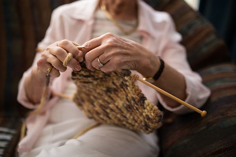 midsection-of-senior-woman-knitting-wool