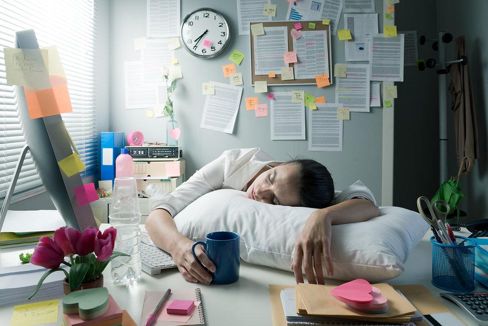 Tired businesswoman at office desk wakin