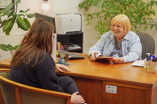 front desk receptionist checks in a patient at a desk
