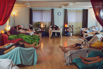 a diverse group of people receivig acupuncture treatment in a peaceful large room with recliners and blankets