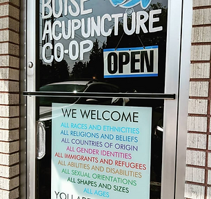 Boise Acupuncte Co-op frot doo with an open sign and a sign of inclusivity
