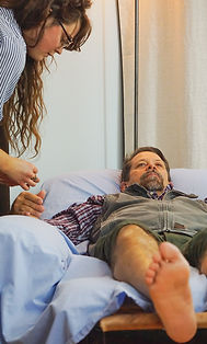 acupuncturist leaning over male patient on a recliner