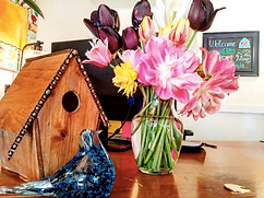 pink lillys in a vase on a desk next to a wooden birdhouse and a blue glass bird
