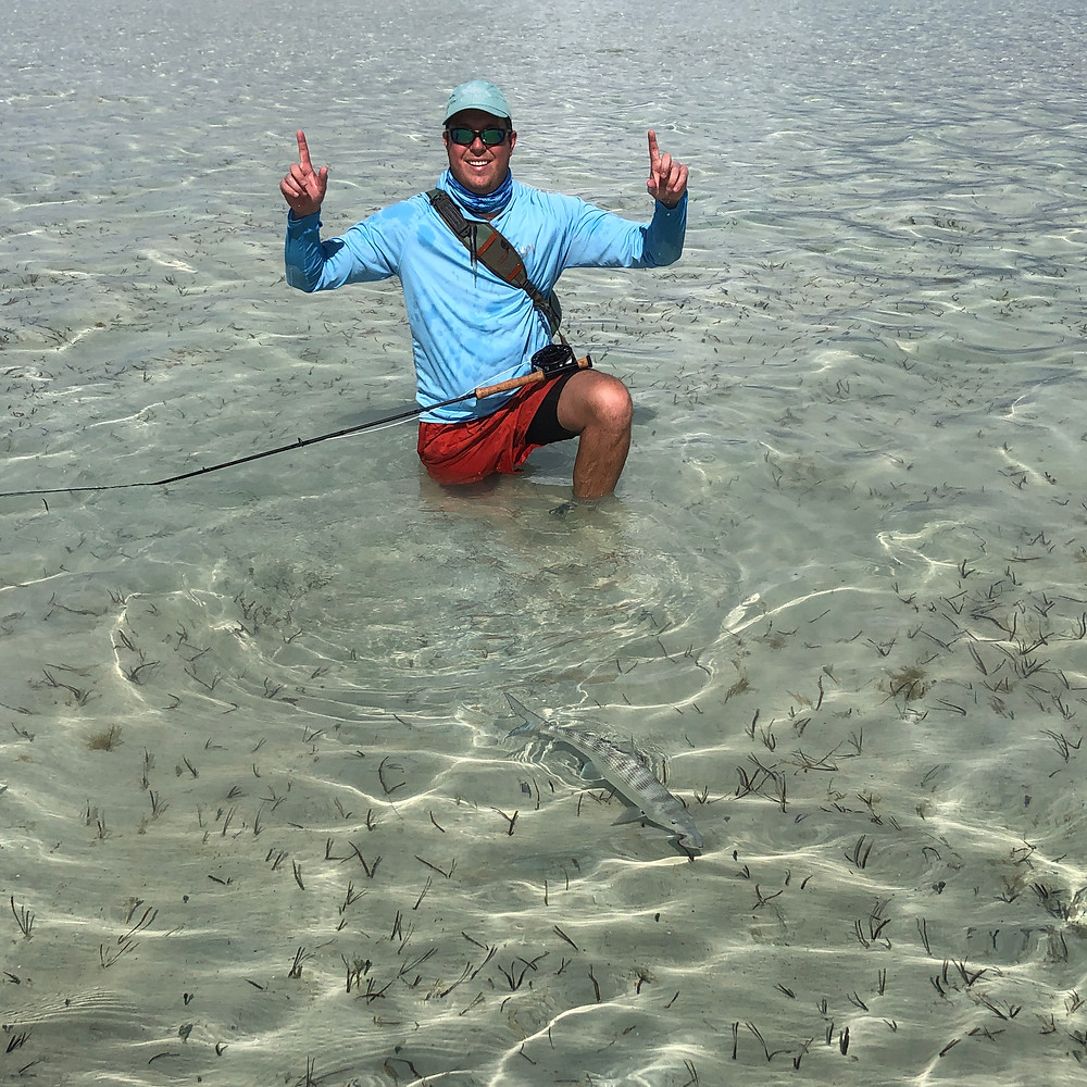 Fly fishermen holds up hands in victory after releasing bonefish