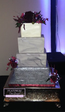 Tiered wedding cake with top tier covered in all white and middle 2 tiers covered in marbled fondant and bottom tier covered in textured fondant.  A large dark red peony along with red roses and small pink sugar flowers decorate the top and sides of the cake along with leaves and led lights. Created by Platinum Cake Designs in Decatur, GA.  Making Memories Sweeter.  #platinumcakedesigns #decatur #atlanta #wedding cake #tieredcake #sugarflower #peony #marbledfondant