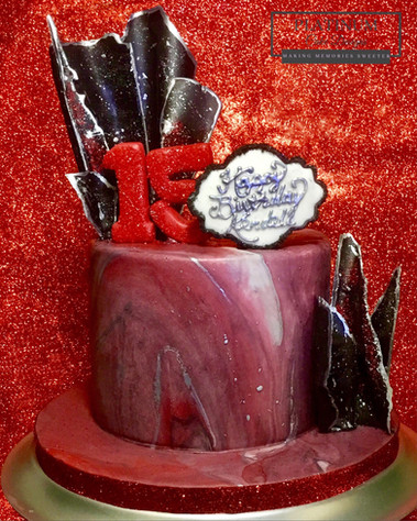 Black and red chocolate sails top this red marbled 15th birthday cake with silver accents.  Created by Platunum Cake Designs in our Decatur, Ga studio.  Making Memories Sweeter #platinumcakedesigns #decatur #fondant #redcake #blackcake #chocolatesails #silver #birthdaycake #15thbirthday